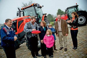 The Malmkar family, seen here with Ron and Lorie Regier on the right, receives the keys to their new tractor at the AGCO manufacturing facility in Beauvais, France.