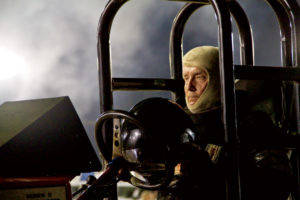 Wearing his fire-resistant hood, a determined and focused Louis Haney waits in line for the pull. He drives the diesel version of Cujo, a tractor well-known for decades in pulling circles.