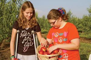 Waters' daughters Taylor and Summer in the orchard.