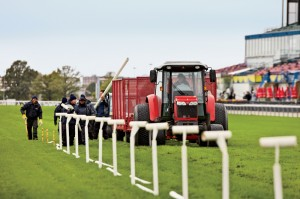 Workers remove temporary inside rails, set by a laser-guided tractor, on the turf course. The rails switch speeding horses to different lanes, resting sections of grass and keeping it healthy.