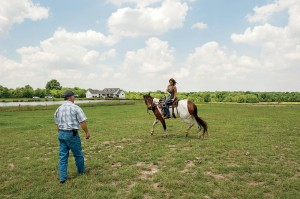 Thalman's daughter, Nicole Kirby, performs a training move with Mingo, one of six horses that lives on the family property.