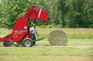 Thalman checks over a 600-pound round bale made with his Hesston 1734 baler.