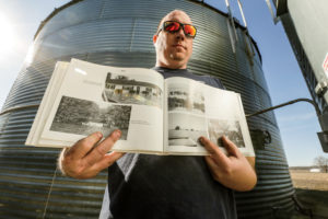 The 1993 flood on the Missouri River was historic and devastating. On the right-hand page of this book, Darren points to a photo of the Littleton place after the waters rose.