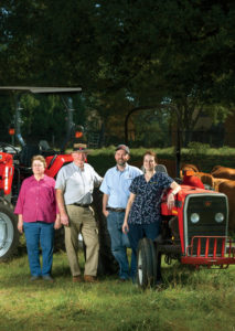 Along with wife Annette, son Nathan, and daughter Aaron, Dr. Lanier Orr (second from left) runs Orr Animal Hospital in Forsyth. He also raises Red Angus cattle—the same color as his Massey Ferguson tractors, his favorite brand—on about 400 total acres in Forsyth, Dawson, and Elbert counties.