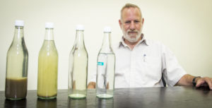 Gal Shoham, a process engineer at Shafdan, with bottles water showing the stages of treatment—from raw wastewater on the far left to that which is treated to the final, tertiary stage.