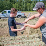 Ronan and Tyler Schmitt, Barry's youngest and oldest sons, respectively, bag a hay sample for moisture testing.