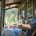 Beth and John Barth sit on the porch of their Bushnell, Fla., home. The couple moved here a decade ago and planted a grove of olive trees.