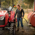 Young girl puts fuel into a Massey Ferguson 1758