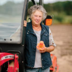 Di Rau holds one of her daylilies while standing next to her Massey Ferguson tractor.